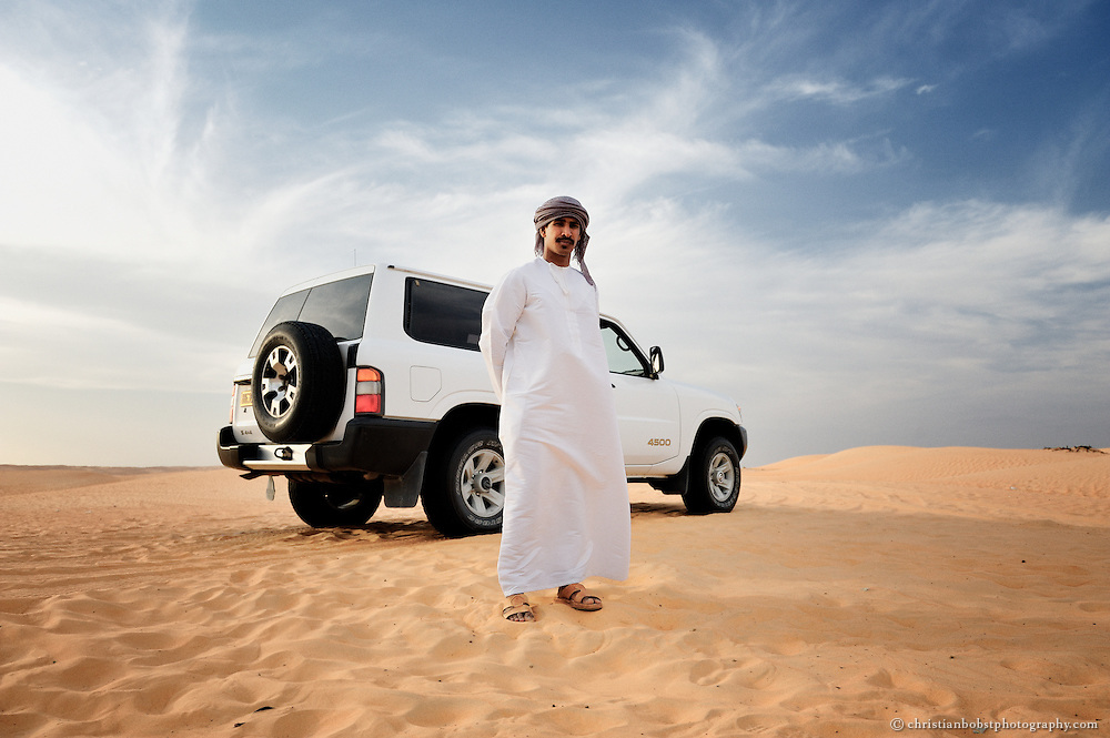 "A young beduin man is posing in front of his modern ""camel"" in Wahiba Sands. Oman, 2011"
