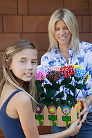 Portrait of a little girl handing over artificial flowers in crate to mother