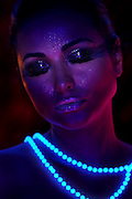 Dreaming woman wearing a glowing pearl necklace.Black light