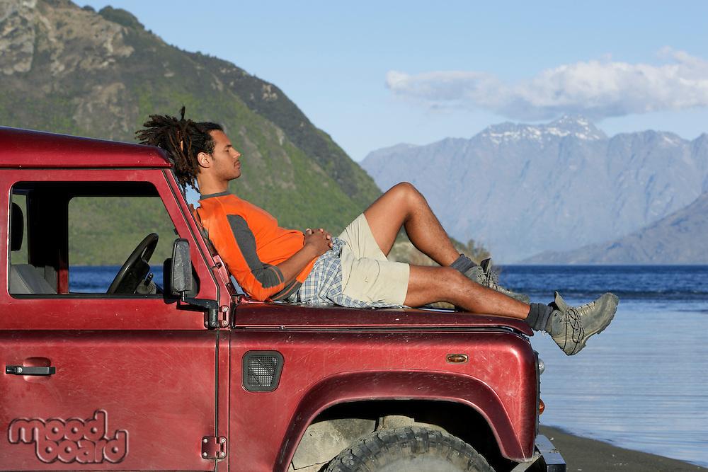 Man lying on hood of jeep near mountain lake