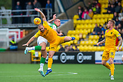 Scott Robinson (#17) of Livingston FC and Scott Brown (#8) of Celtic FC contest a header, as Robbie Crawford (#16) of Livingston FC watches on, during the Ladbrokes Scottish Premiership match between Livingston FC and Celtic FC at The Tony Macaroni Arena, Livingston, Scotland on 6 October 2019.