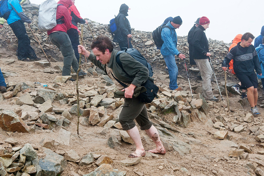 Barefooted pilgrim Don O'Meara from Ballinhassig, Co. Cork makes his way up the mountain for the first time on pilgrimage to  Croagh Patrick, Co. Mayo. Pic: Michael Mc Laughlin Thousands of pilgrims navigate up and down the rugged slopes of croagh Patrick in honour of our Patron Saint, Saint Patrick, Ireland's Holy Mountain, Co. Mayo. Pic: Michael Mc Laughlin