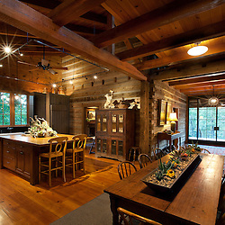 photo of log cabin interior showing kitchen, breezeway, and dining area