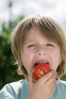 Boy eating tomato in garden portrait