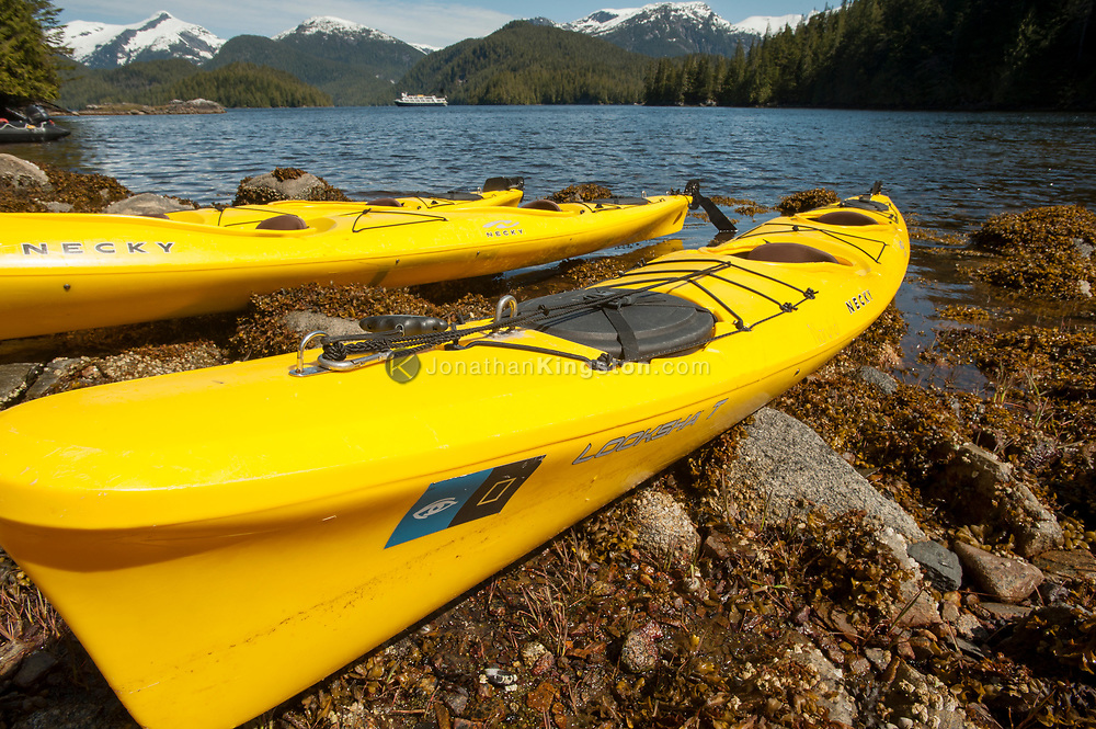 Yellow kayaks on a rocky shore with a ship in the background in Klewnuggit Inlet Marine Provincial Park, British Columbia, Canada.