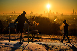 © Licensed to London News Pictures. 29/12/2016. London, UK. Joggers stop on Parliament Hill on Hampstead Heath London to watch the sunrise over the city of London on another cold winter morning. Most of the UK has woken to freezing temperatures. Photo credit: Ben Cawthra/LNP