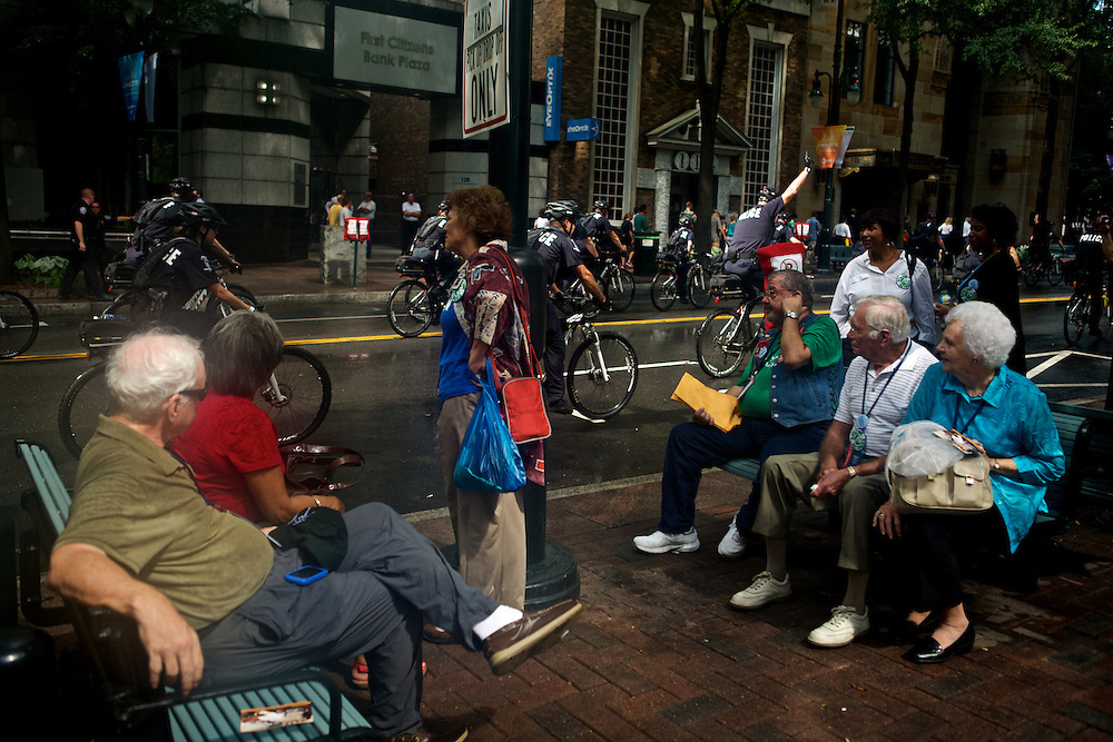 Attendees of the 2012 Democratic National Convention watch as police [atrol the streets on bicycles Tuesday, September 4, 2012 in Charlotte, NC.