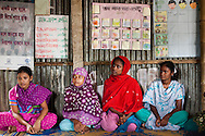 Young girls sit in a group at a monthly meeting of a Children's Group in Bhashantek Basti (Slum) in Zon H, Dhaka, Bangladesh on 23rd September 2011. The Bhashantek Basti Children's Group is run by children for children with the facilitation of PLAN Bangladesh and other partner NGOs. Slum children from ages 8 to 17 run the group within their own communities to protect vulnerable children from child related issues such as child marriage. About 20150 people live in the Bhashantek urban slum, with an average household size of 5 in housing sizes of 8 x 9ft made of bamboo, tin sheets and scrap materials. The average annual income is USD 200. Photo by Suzanne Lee for The Guardian
