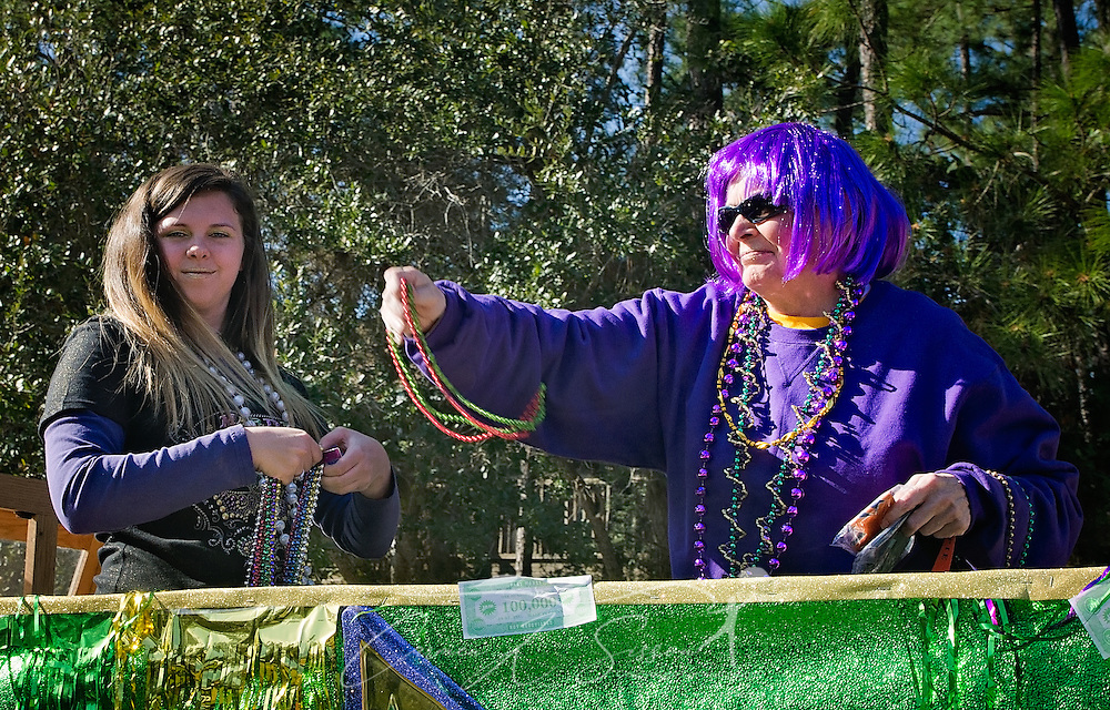 Employees of The First Bank throw beads in Dauphin Island's first People's Parade during Mardi Gras, Feb. 4, 2017, in Dauphin Island, Alabama. French settlers held the first Mardi Gras in 1703, making Mobile's celebration the oldest Mardi Gras in the United States. The first parade of the season is traditionally held on Dauphin Island and draws thousands. (Photo by Carmen K. Sisson/Cloudybright)