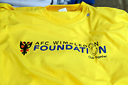 AFC Wimbledon foundation t shirt during the EFL Sky Bet League 1 match between AFC Wimbledon and Accrington Stanley at the Cherry Red Records Stadium, Kingston, England on 6 April 2019.