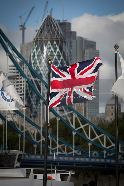 The Union Jack flag flies in the foreground of Tower Bridge and construction work in progress next to the Swiss Re Building (aka the Gherkin) in the capital's financial district (The Square Mile) behind, on 5th October, 2017, in London, England.