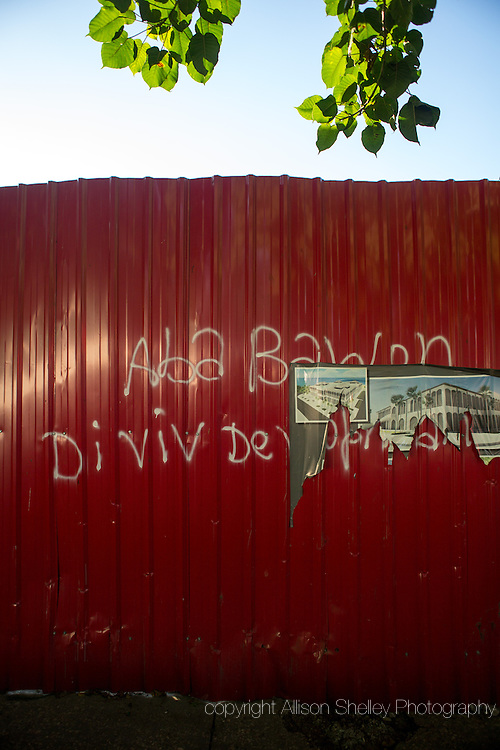 """Graffiti reading """"Down with the baron. Long live development,"""" is seen on a construction fence, along with a picture of the replacement Ministry of Economy and Finance, stands where the former ministry, destroyed in the 2010 quake used to be, in Port-au-Prince, Haiti, January 4, 2015.  The building was deconstructed brick by brick by local residents who sold the materials to construction companies.  The lot behind the fence remains empty. The """"baron"""" refers to President Michel Martelly, who will rule by decree if an agreement with parliament allowing elections does not happen by January 12, the five year anniversary of the quake."""