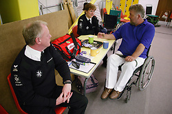 Man with disability chatting to staff at a bowls event held at Solihull Indoor Bowls Centre,