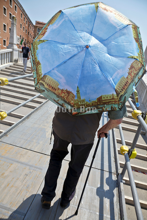 senior man walking on the Riva degli Schiavoni during a hot day in Venice Italy