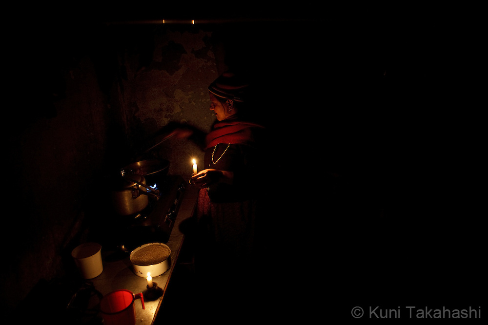 (Jan 7, 2012 - Kathmandu, Nepal).Woman cooks under candle lights during power outage in Kathmandu, Nepal, on Jan 7, 2012. For the last several years, nearly 800,000 people of the capital city faced up to 16 hours of blackouts every day, mainly caused by political instability. Nepal is said to be second only to Brazil in terms of water resources but the government has been incapable of harnessing hydropower..(Photo by Kuni Takahashi)
