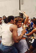 A man shoving an icecream into his woman's armpit, Notting Hill carnival, London, UK 1980's