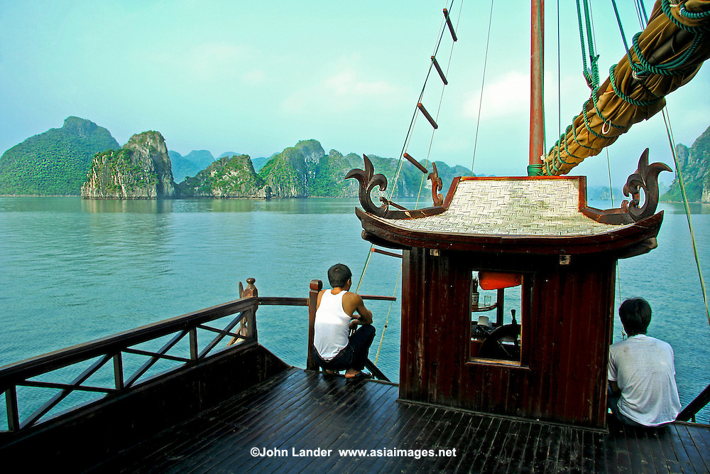 Halong Bay Boat Crew - Crew taking a break on the deck of a junk on Halong Bay enjoying the UNESCO World Heritage views of Halong Bay even though they see these sights every working day, it is hard not to appreciate nevertheless.