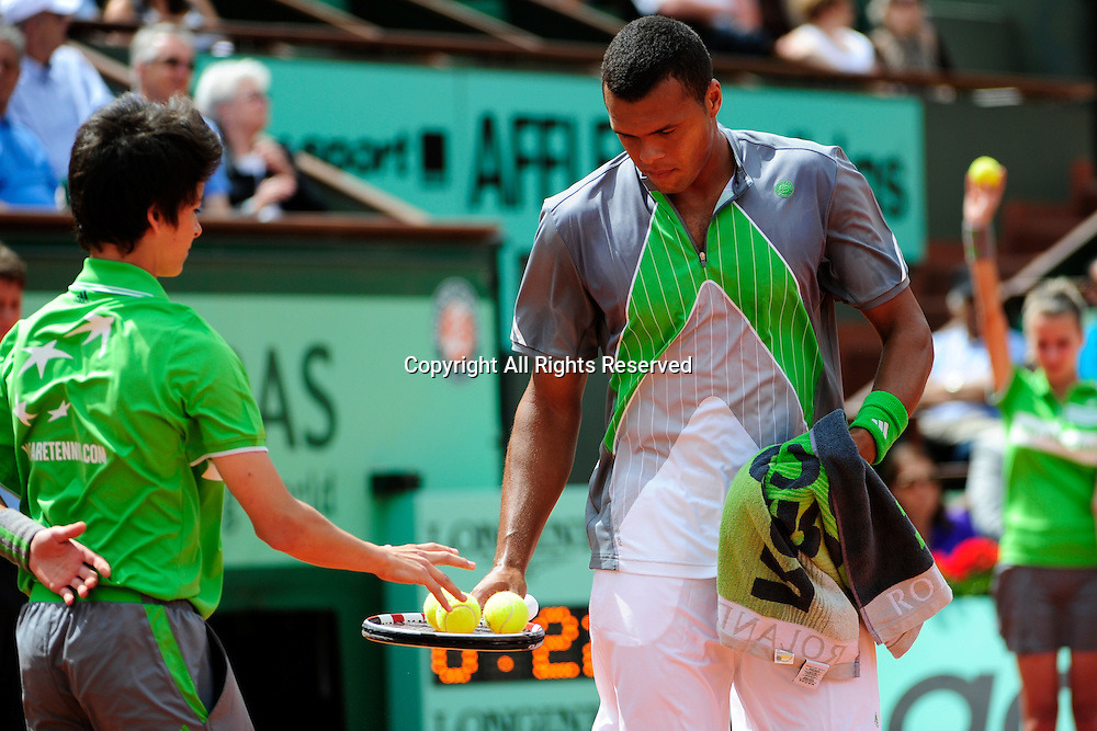 22.05.2011 French Open Tennis from Roland Garros Paris. Jo-Wilfried Tsonga of France receives tennis balls from a ball boy in his match against Jan Hajek of the Czech Republic on day one of the French Open tennis championships. The match was won by Tsonga 6-3, 6-2, 6-2.