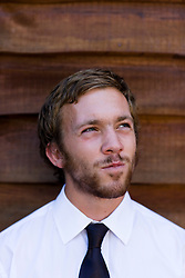 Close up of a young businessman standing against a wood wall looking up