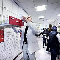 Nederland, Amsterdam , 28 mei 2013.<br /> Na zo'n 100 jaar houdt apotheek de Vijzel op Ceintuurbaan 398 op met bestaan vanwege de economische crisis.<br /> Op de foto dhr. Sollie zoekt enkele medicijnen op in de apotheek.<br /> Foto:Jean-Pierre Jans