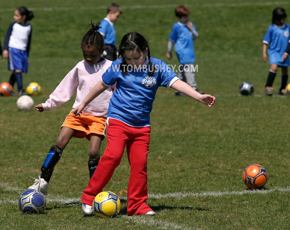 Two girls practice dribbling the ball during the first day of Middletown youth soccer practice at Watts Park in Middletown, N.Y.April 16, 2005.