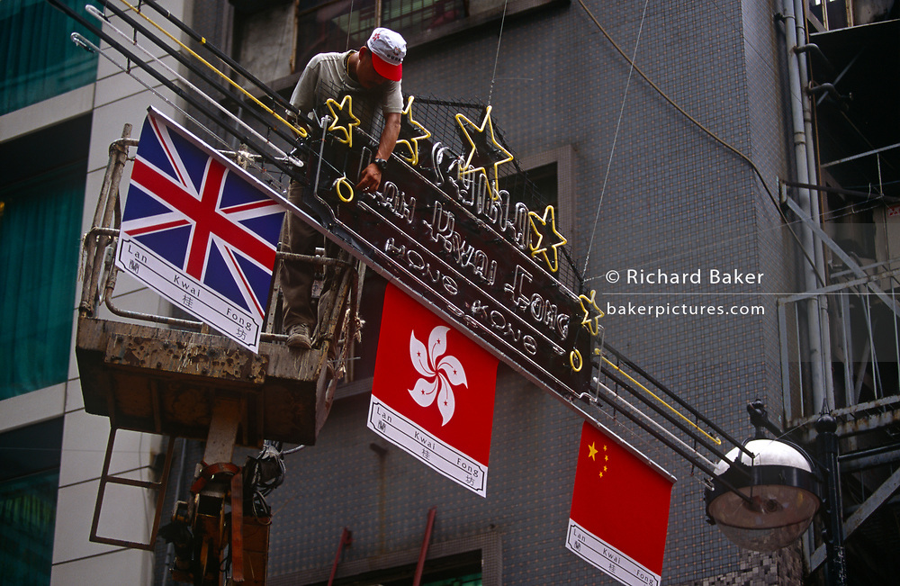 The flags of Britain, Hong Kong and Peoples' Republic of China fly together above the streets of Central, the day after the Handover of sovereignty from Britain to China, on 30th June 1997, in Hong Kong, China. Midnight signified the end of British rule, and the transfer of legal and financial authority back to China. Hong Kong was once known as 'fragrant harbour' (or Heung Keung) because of the smell of transported sandal wood.