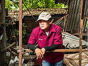 03 SEPTEMBER 2016 - BANGKOK, THAILAND:  A Bangkok city worker relaxes in a home he is tearing down during an operation to evict people from the Pom Mahakan community. Hundreds of people from the Pom Mahakan community and other communities in Bangkok barricaded themselves in the Pom Mahakan Fort to prevent Bangkok officials from tearing down the homes in the community Saturday. The city had issued eviction notices and said they would reclaim the land in the historic fort from the community. People prevented the city workers from getting into the fort. After negotiations with community leaders, Bangkok officials were allowed to tear down 12 homes that had either been abandoned or whose owners had agreed to move. The remaining 44 families who live in the fort have vowed to stay.     PHOTO BY JACK KURTZ