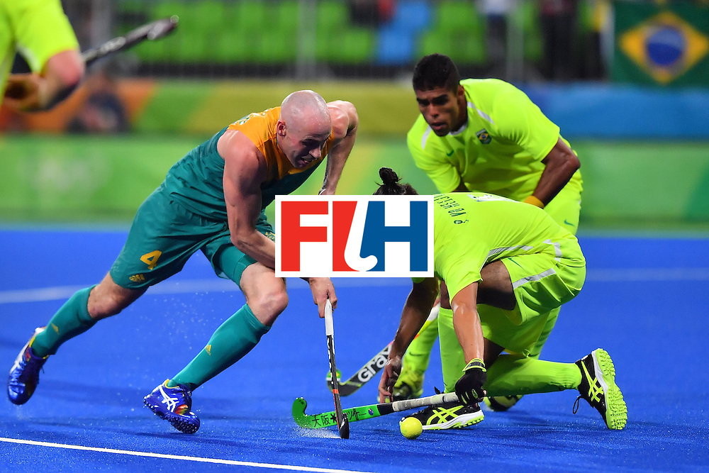 Australia's Glenn Turner (L) is tackled during the mens's field hockey Australia vs Brazil match of the Rio 2016 Olympics Games at the Olympic Hockey Centre in Rio de Janeiro on August, 12 2016. / AFP / Carl DE SOUZA        (Photo credit should read CARL DE SOUZA/AFP/Getty Images)