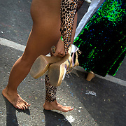 Notting Hill Carnival August 28th 2017. West London, England. A dancer wearing a leopard skin leotard and with sore feet carries her golden heeled sandals.