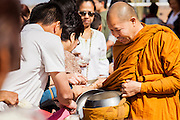 "11 MARCH 2012 - CHANDLER, AZ:     The Abbot at Wat Pa in Chandler, AZ, collects food in his alms bowl during Makha Bucha day services Sunday. Magha Puja (also spelled Makha Bucha) Day marks the day 2,500 years ago that 1,250 Sangha came spontaneously to see the Buddha who preached to them on the full moon. All of them were ""Arhantas"" or Enlightened Ones who had been personally ordained by the Buddha. The Buddha gave them the principles of Buddhism, called ""The Ovadhapatimokha."" Those principles are: to cease from all evil, to do what is good, and to cleanse one's mind. It is one of the most important holy days in the Theravada Buddhist tradition. At the temple, people participate in the ""Tum Boon"" (making merit by listening to the monk's preaching and giving a donation to the temple), the ""Rub Sil"" (keeping of the Five Precepts including the abstinence from alcohol and other immoral acts) and the ""Tuk Bard"" (offering food to the monks in their alms bowls). It is a day for veneration of the Buddha and his teachings. It's a legal holiday in Thailand, Laos, Cambodia and Myanmar (Burma).    PHOTO BY JACK KURTZ"