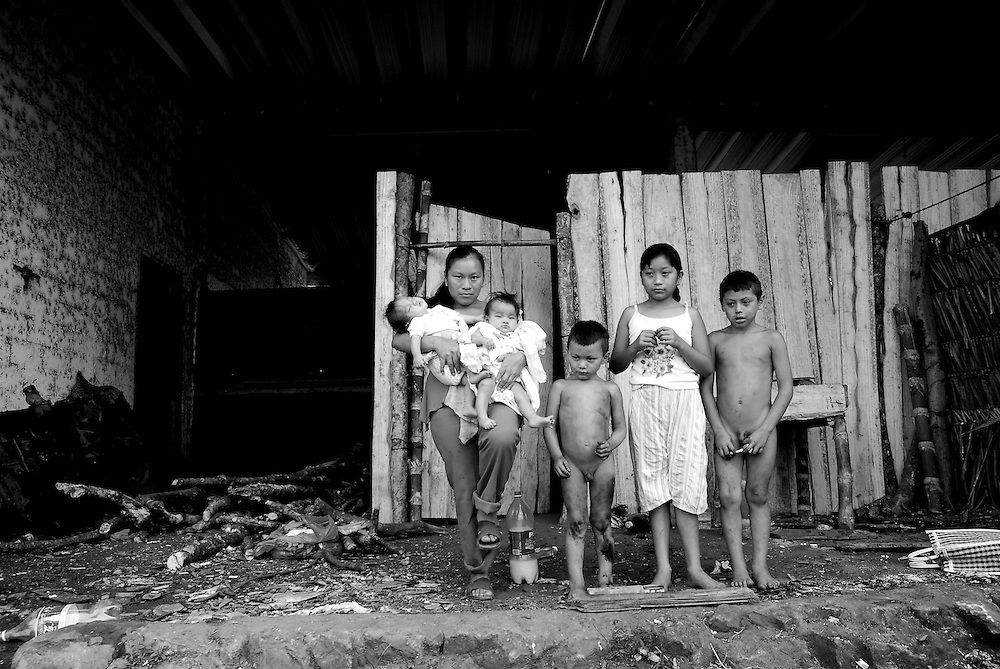 Maria Rosario Bacat Ruiz poses for a family portrait in front of her small home with her five children, Ruth, Jesus, Jose and six-month old twins Gabriela and Graciela. Bacat lives in impoverished conditions in a camp for migrant sugarcane laborers and their families outside of Tuxtepec in southern Mexico. All seven members of her family sleep on overlapping woven straw mats in their alloted room in the camp and share cooking and bathroom facilities with other families working the sugarcane harvest.