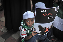 Image licensed to i-Images Picture Agency. 18/07/2014. Kuala Lumpur,Malaysia.A young Demonstrators hold placards as they protest against Israel's military action in Gaza during a demonstration in front of the US embassy in Kuala Lumpur on July 18, 2014.Picture by Mohd Firdaus / i-Images