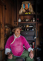 Senior tibetean community leader in his home sitting in front of his worship shine.