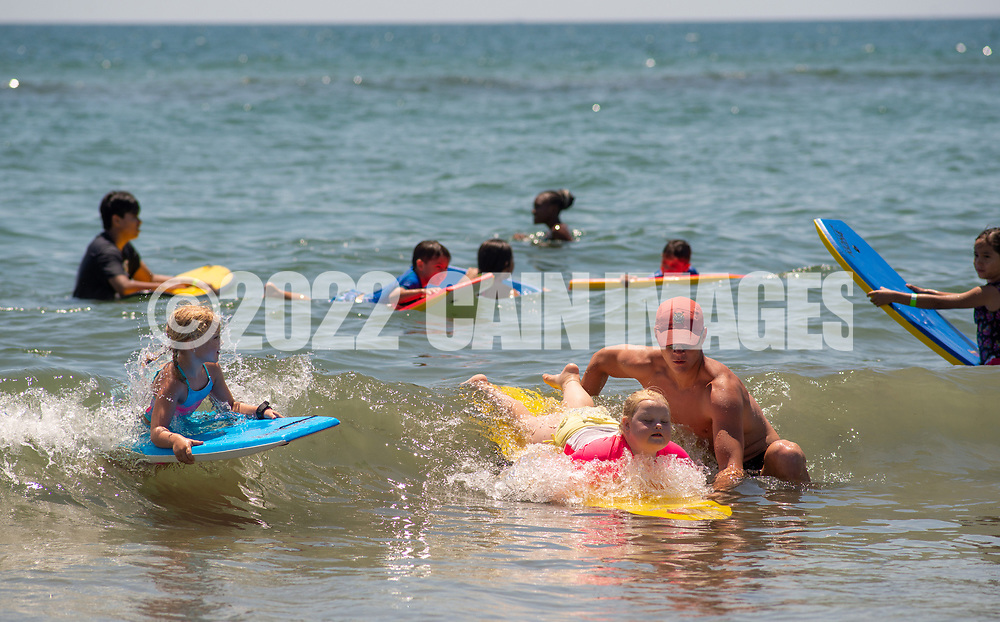 Lifeguard Ryan Comas (right), 20, of Philadelphia pushes Sage Praweckyj, 8, on her paddle board as her sister Veronica Praweckyj, 6, watches during the 11th annual 21 Down Beach Day Monday, July 15, 2019 at Schellenger Street beach in Wildwood, New Jersey. Every summer, the Wildwood Beach Patrol opens Lincoln Ave Beach for kids with down syndrome and their families for 21 Down Beach Day. Often, kids with down syndrome aren't comfortable in the ocean. Their parents can't just relax and watch them frolic. But on July 15th, the kids swim with seasoned Wildwood lifeguards on soft-top paddle boards. (Photo by William Thomas Cain / CAIN IMAGES)