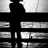 Newport Beach Fisherman Pier Fishing Picture. Balboa Pier is located on Balboa Peninsula and is a popular spot in Orange County for fishing in the Pacific Ocean.