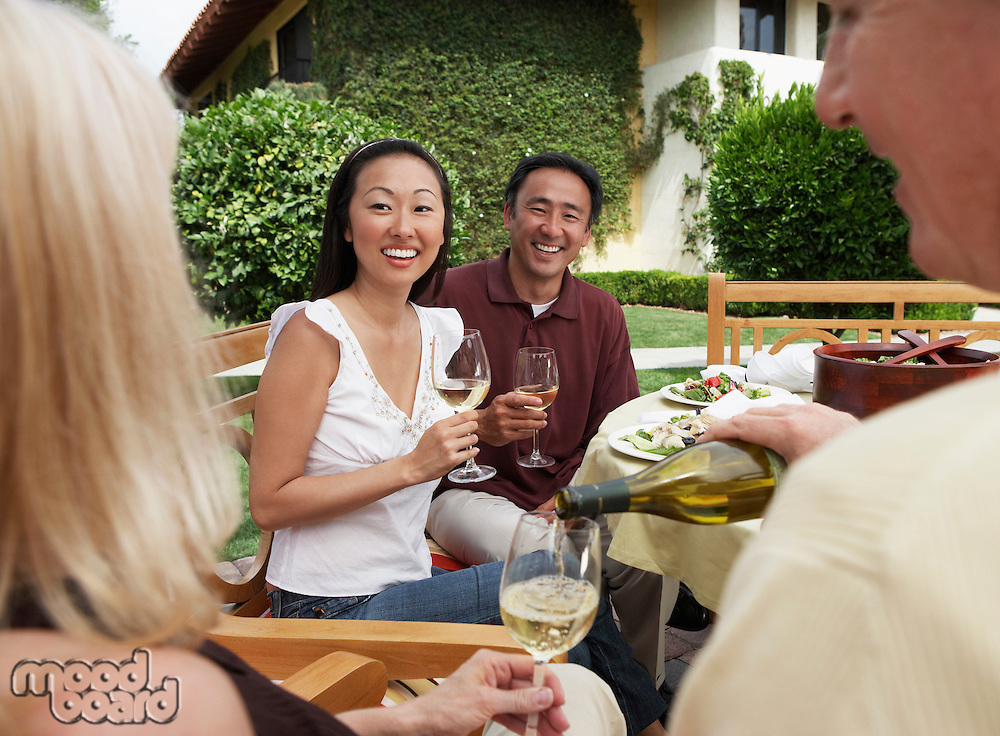 Friends having dinner and drinks in garden