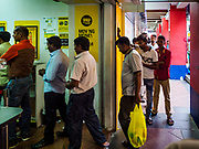 "09 JULY 2017 - SINGAPORE: Guest workers from the Indian sub-continent line up to get into a Western Union to send money back to their families. There are hundreds of thousands of guest workers from the Indian sub-continent in Singapore. Most work 5 ½ to six days per week. On Sundays, the normal day off, they come into Singapore's ""Little India"" neighborhood to eat, drink, send money home, go to doctors and dentists and socialize. Most of the workers live in dormitory style housing far from central Singapore and Sunday is the only day they have away from their job sites. Most work in blue collar fields, like construction or as laborers.    PHOTO BY JACK KURTZ"