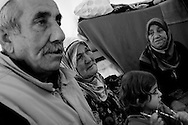 An elderly woman cries as she hears news of recent attacks by the Syrian military in her hometown of Jisr Ash-Shughur, from where her daughter and grandchildren are still trying to flee to the Turkish border. Reyhanli refugee camp, Turkey. 14th March 2012