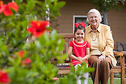 Senior Woman Sitting on a Bench Enjoying the Outdoors with her Granddaughter