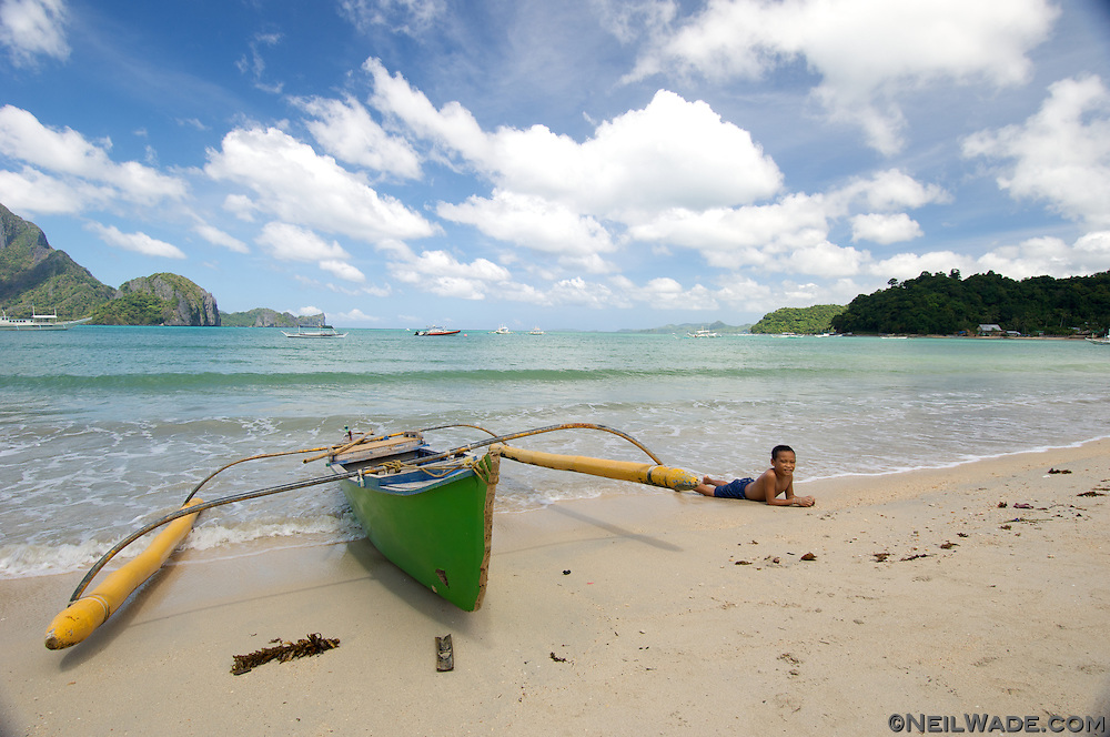 An out-rigger boat sits on the beach in El Nido Town, Philippeans.