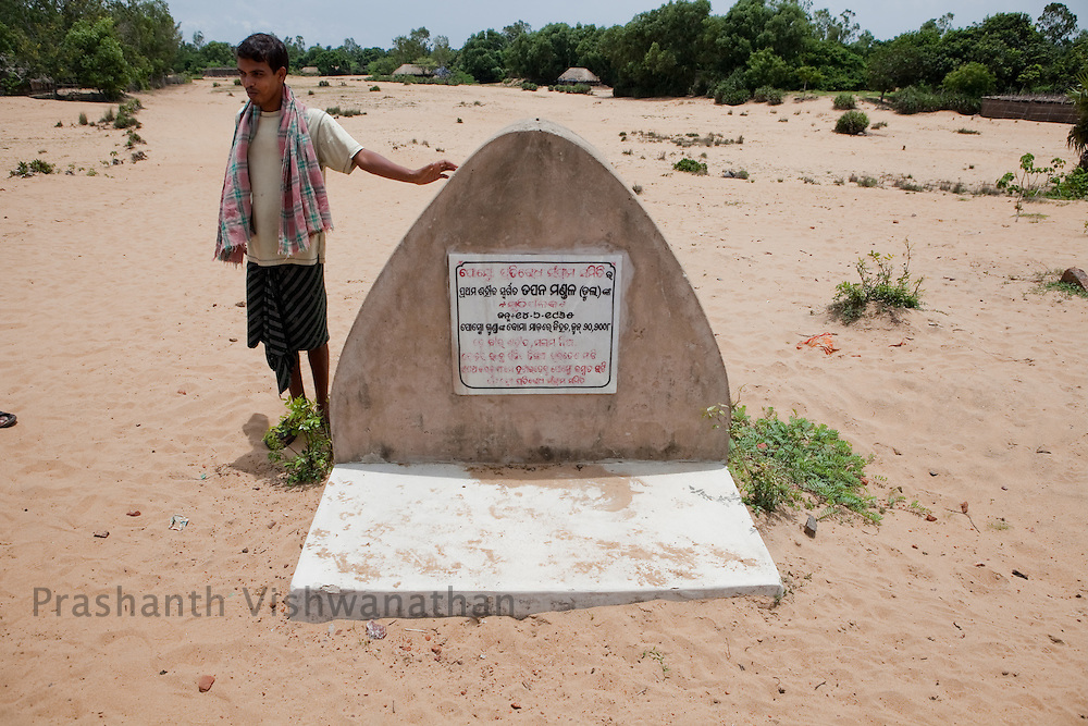 A farmer points out the tomb of the first martyr of the anti POSCO movement Tapan Mandal, at the plot alloted to POSCO steel company in Patana, Orissa, India, on Thursday July 1, 2010. Photographer: Prashanth Vishwanathan/Bloomberg News