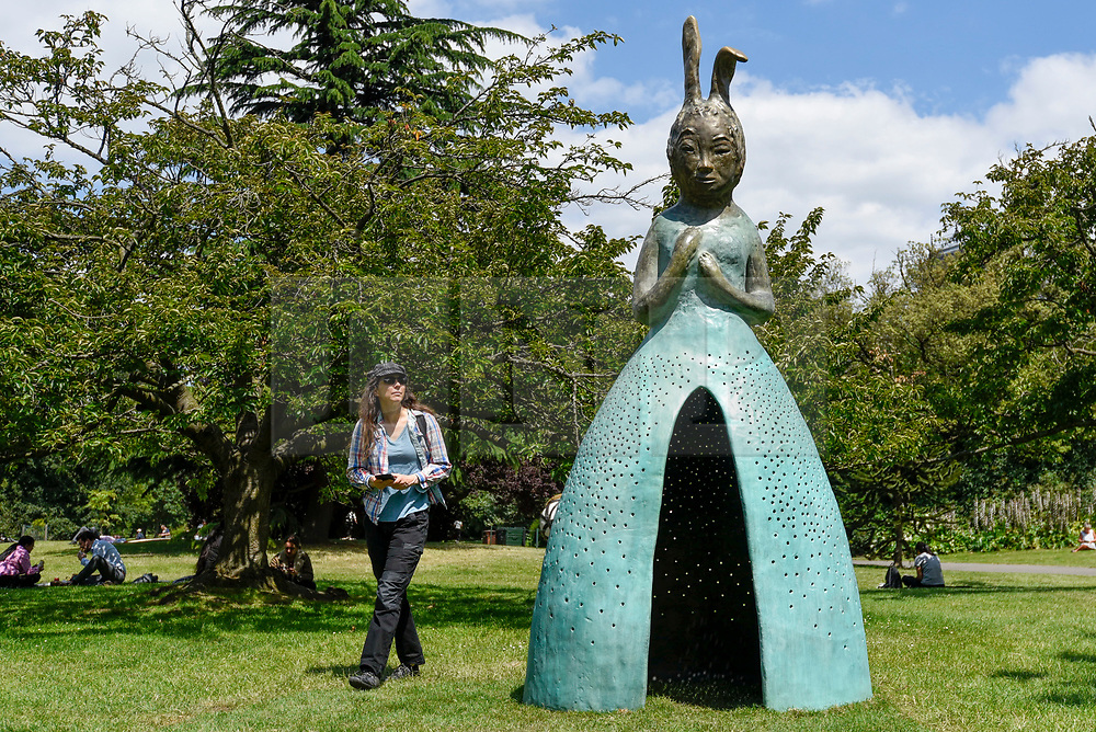 """© Licensed to London News Pictures. 03/07/2019. LONDON, UK. A woman views """"Usagi Kannon II"""", 2013-18, by Leiko Ikemura. Frieze Sculpture opens in Regent's Park, London's largest free display of outdoor art.  Works from 23 international artists are on display 3 July to 6 October 2019.  Photo credit: Stephen Chung/LNP"""