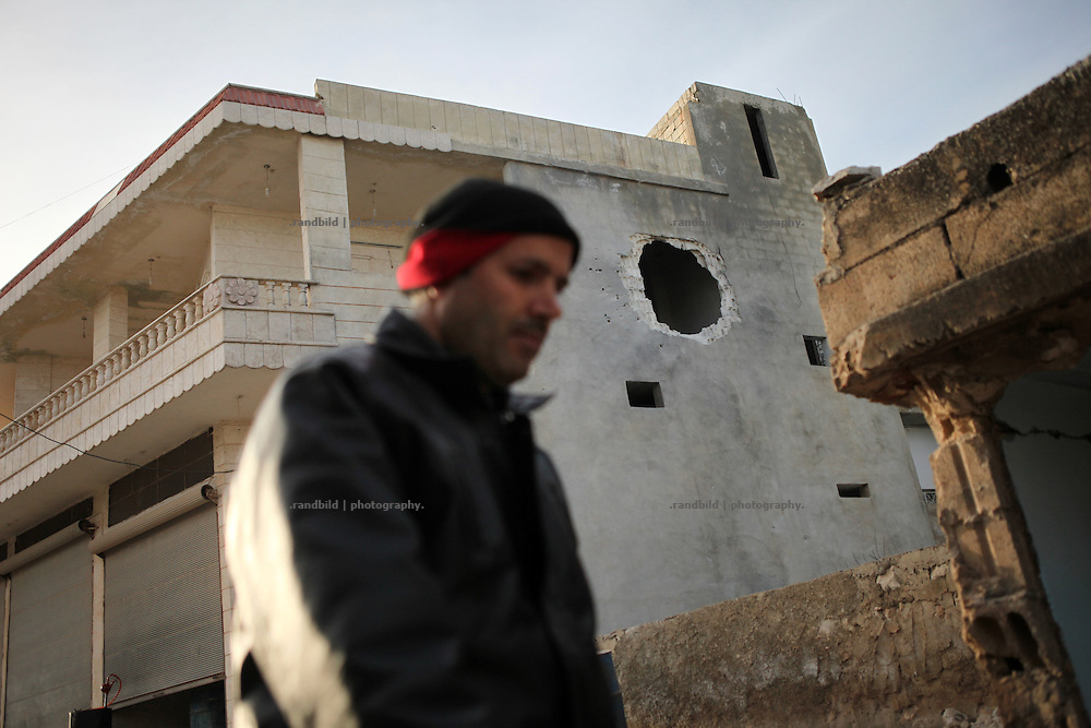 A man pass along a multi-story building hit by rocket. On 22. February the syrian army attacked the village of Kureen, Province of Idlib, Syria. Kureen was among the first villages in the northwest of Syria controlled by the opposition. Some villagers and members of the defence units escaped to surrounding olive orchards, when the attack begun in the early morning. A majority of the inhabitants didn´t manage to escape. The heavy shelling lasts 7 houres. Soldiers searched all houses, burnt some of them down, loote shops, stole cars and furniture. About 60 motorcycles were burnt down. Tanks demolished several houses. 6 men were executed. One woman died as a result of an heart attack.