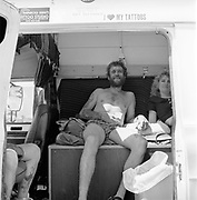 Man with tattoos sitting in caravan, Glastonbury, Somerset, 1989