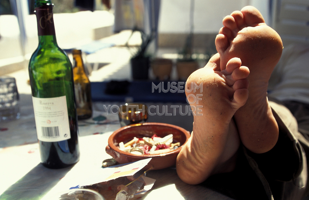 The morning after a night out a man puts his tired feet up, Ibiza, 2000s.