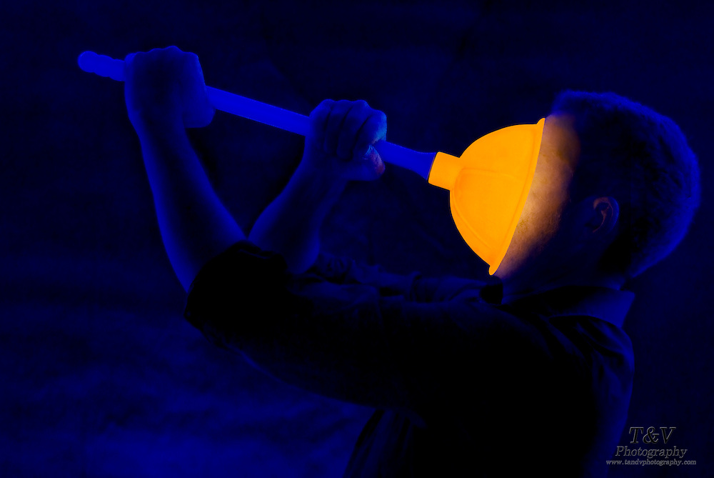 Man struggles with a toilet plunger that is stuck to his face.Black light