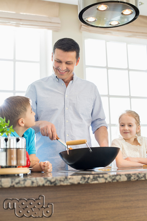 Happy man with children preparing food in kitchen