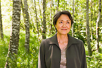 Portrait of an Asian businesswoman in her fifties standing in a green lush green forest..Model Release: 20080616_MR_A