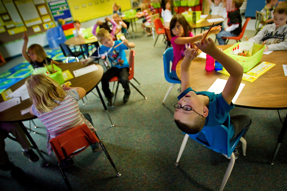 Torrin Wagner, 6, looks back toward the projector screen to see the next step of his first grade penmanship classwork Friday at Prairie View Elementary in Post Falls. The school saw a rise in the student population of 13 percent over last year.