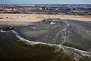 Nederland, Zuid-Holland, Monster, 18-03-2009; Versterking van de kust van Delfland tussen Ter Heijde en 's-Gravenzande door middel van zandsuppletie. Het zand wordt opgezogen door een sleephopperzuiger en naar land gebracht via een persleiding. Omdat het zand hoog op het strand opgespoten moet worden, zijn er dammen van zand rond de monding van de pijp aangelegd om het zand tegen te houden. Het overtollig water loopt naar opzij terug naar zee. De Delflandse kust is een van de 'Zwakke Schakels' in de zeewering. De Kerk van Monster achter de duinen met de kassen van het Westland..The coast of Delfland, between Hoek van Holland and The Hague, is been between strengthened by means of sand-supplementation. The sand is sucked up by a dredger and brought ashore by means of high pressure pipes (mouth of the pipe in the middle). Bulldozers have made dams around this mouth to keep the new sand in place when it is sprayed high on the beach, the surplus of water flows back to the sea. .Swart collectie, luchtfoto (toeslag); Swart Collection, aerial photo (additional fee required); .foto Siebe Swart / photo Siebe Swart